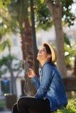 Piękna młoda kobieta słucha muzyka na telefonie komórkowym Obrazy Stock