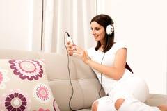 Piękna młoda kobieta słucha muzyka w hełmofonach Fotografia Stock