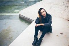 Piękna młoda kobieta siedzi na betonowych progach Zdjęcia Royalty Free