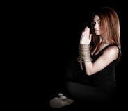 Piękna młoda kobieta siedzi na podłoga z wiązanymi rękami Obrazy Stock