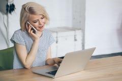 Piękna młoda kobieta siedzi przed laptopem i mówi na telefonie Zdjęcie Stock