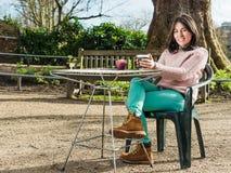 Piękna młoda kobieta Siedzi Samotnie w kawiarni Plenerowej Zdjęcie Royalty Free