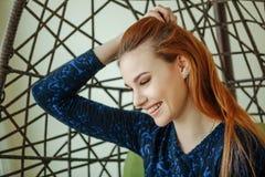 Piękna młoda kobieta siedzi w breloczka krześle w pokoju zdjęcia royalty free