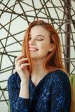 Piękna młoda kobieta siedzi w breloczka krześle w pokoju fotografia stock