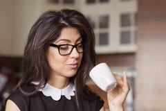 Piękna młoda kobieta siedzi w domu, pijący kawę obrazy stock
