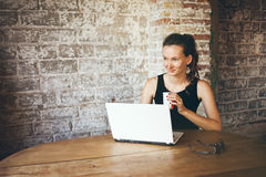 Piękna młoda kobieta siedzi w kawowym domu i używa laptop, pijący kawiarni, patrzeje lewą stronę Fotografia Royalty Free