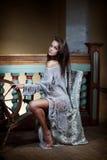 Piękna młoda kobieta siedzi z kądzielą dla robić przędzy Zdjęcie Stock