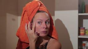 Piękna młoda kobieta sprawdza jej twarz w lustrze przy łazienką zdjęcie wideo