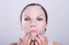 Piękna młoda kobieta stawia starzenie się maskę na jej twarzy Zdjęcia Stock