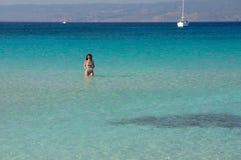 Piękna młoda kobieta sunbathing przy wspaniałą Simos plażą w Grecja Obrazy Royalty Free