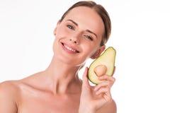 Piękna młoda kobieta trzyma część avocado Obraz Stock