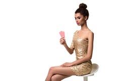 Piękna młoda kobieta trzyma dwa karty odizolowywająca na bielu w ona ręka Zdjęcie Royalty Free