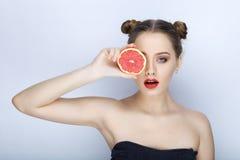 Piękna młoda kobieta trzyma grapefruitowego zdrowego łasowania organi z perfect zdrowego skóry uczesania śmiesznego modnego makeu Zdjęcia Stock