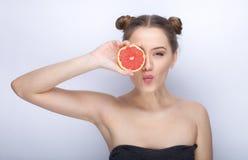 Piękna młoda kobieta trzyma grapefruitowy zdrowego z perfect błyszczącego glansowanego zdrowego skóry uczesania śmiesznego modneg Fotografia Royalty Free