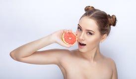 Piękna młoda kobieta trzyma grapefruitowy zdrowego z perfect błyszczącego glansowanego zdrowego skóry uczesania śmiesznego modneg Obraz Royalty Free
