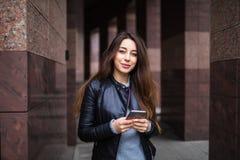 Piękna młoda kobieta używa app w jej smartphone przyrządzie wysyłać wiadomość tekstową przed budynku tłem Zdjęcie Stock