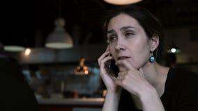 Piękna młoda kobieta używa smartphone w kawiarni podczas gdy czekający rozkaz Kobieta opowiada na telefonie komórkowym zbiory wideo