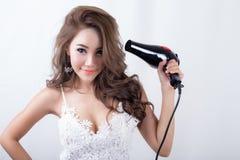 Piękna młoda kobieta Używa Włosianą dmuchawę Zdjęcia Stock
