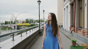 Piękna młoda kobieta w błękit sukni odprowadzeniu w mieście z torba na zakupy, spojrzenia wokoło, wolny mo stedicam strzał zbiory wideo