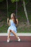 Piękna młoda kobieta w biały błękit paskującej sukni ma zabawę na huśtawce w miasto parku Zdjęcie Royalty Free