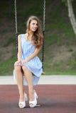 Piękna młoda kobieta w biały błękit paskującej sukni ma zabawę na huśtawce w miasto parku Obraz Stock