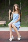 Piękna młoda kobieta w biały błękit paskującej sukni ma zabawę na huśtawce w miasto parku Obrazy Stock