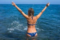 Piękna młoda kobieta w bikini na plażowej chełbotanie wodzie - wizerunek Nieprawdopodobny Santorini, Grecja - obrazy stock