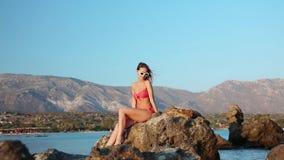 Piękna młoda kobieta w bikini obsiadaniu na skałach zdjęcie wideo
