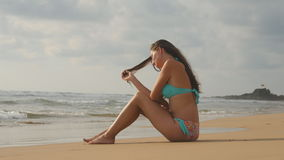 Piękna młoda kobieta w bikini obsiadaniu na złotym piasku na morze plaży Garbnikująca dziewczyna relaksuje na perfect raju brzeg Fotografia Royalty Free