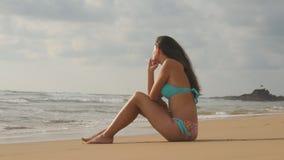 Piękna młoda kobieta w bikini obsiadaniu na złotym piasku na morze plaży Garbnikująca dziewczyna relaksuje na perfect raju brzeg Zdjęcia Royalty Free