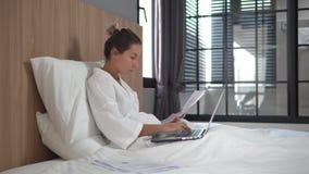 Piękna młoda kobieta w domu, siedzi w jej łóżkowej, ruchliwie adalt dziewczynie w białym bathrobe, włosy zbierający w górę babecz zdjęcie wideo