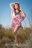 Piękna młoda kobieta w dzikich kwiatów polu na niebieskiego nieba tle Portret atrakcyjna czerwona włosiana dziewczyna z długie wł Fotografia Royalty Free
