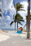 Piękna młoda kobieta w hamaku na plaży na tle drzewka palmowe i morze zdjęcie stock