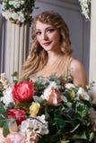 Piękna młoda kobieta w jaskrawych sukniach pozuje w wnętrzu Zdjęcie Stock
