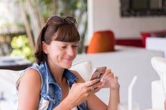 Piękna młoda kobieta w kawiarni używać zastosowanie wysyłać sms wiadomość w jej smartphone przyrządzie bali obraz stock