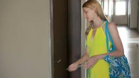 Piękna młoda kobieta w kolor żółty sukni otwiera drzwi z kluczami i wchodzić do jej mieszkanie zbiory