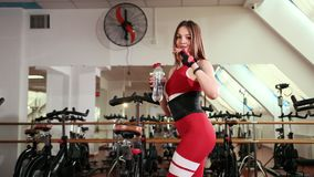 Piękna młoda kobieta w kostiumu jest wodą pitną po lekcji quench pragnienie zdjęcie wideo