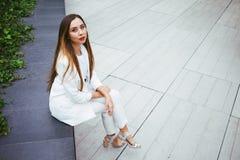 Piękna młoda kobieta w kostiumu siedzi w podwórku budynek biurowy Obrazy Royalty Free