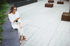 Piękna młoda kobieta w kostiumu siedzi w podwórku budynek biurowy i używa jej smartphone Zdjęcie Royalty Free