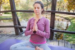 Piękna młoda kobieta W Medytacyjnej pozie Na Drewnianym moście Przy parkiem zdjęcie royalty free