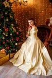 Piękna młoda kobieta w pięknym smokingowym obsiadaniu przy choinką z prezentami, bożymi narodzeniami i nowym rokiem, fotografia royalty free