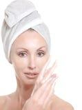 Piękna młoda kobieta w ręczniku z kosmetyczną śmietanką obraz stock