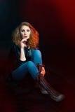 Piękna młoda kobieta w rockowym stylowym obsiadaniu na podłoga Zdjęcie Stock