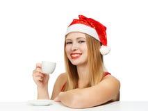 Piękna młoda kobieta w Santa Claus kapeluszowym obsiadaniu przy stołów wi Zdjęcie Royalty Free