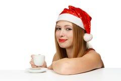 Piękna młoda kobieta w Santa Claus kapeluszowym obsiadaniu przy stołów wi Zdjęcia Stock