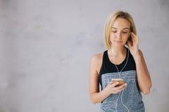 Piękna młoda kobieta w sportach jest ubranym i słuchawki słuchają muzyka używać smartphone Obraz Royalty Free