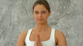Piękna młoda kobieta w sportswear ćwiczy joga patrzeć kamerę i podczas gdy siedzący w lotosowej pozyci z namaste Obraz Stock