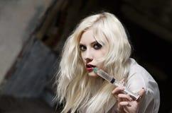Piękna młoda kobieta w wizerunku pielęgniarka z strzykawką w ręce fotografia stock