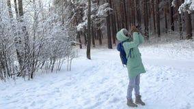 Piękna młoda kobieta w zimy odzieży, mitynkach i wełna kapeluszu, fotografuje śnieżnego las trykotową kamerą zbiory wideo