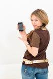 piękna młoda kobieta wystawia telefon komórkowego Obrazy Royalty Free